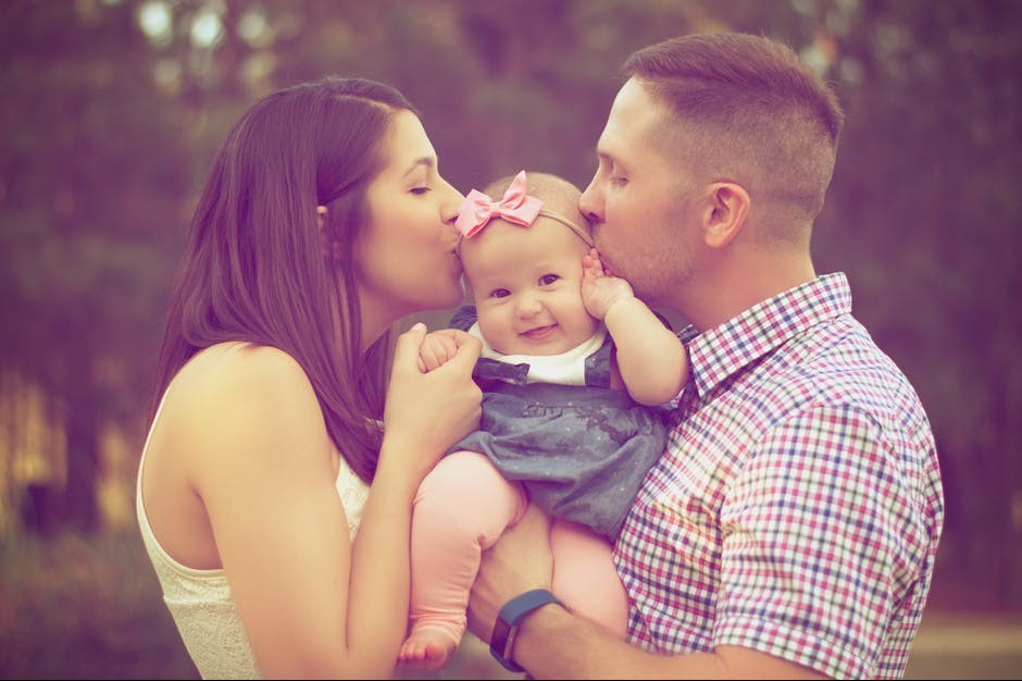 couple kissing their baby